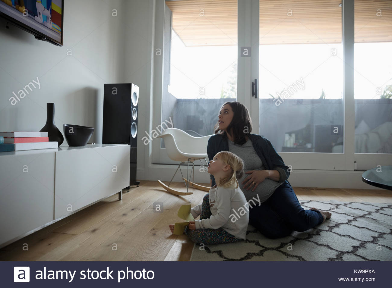 Pregnant mother and toddler daughter watching TV on living room floor - Stock Image