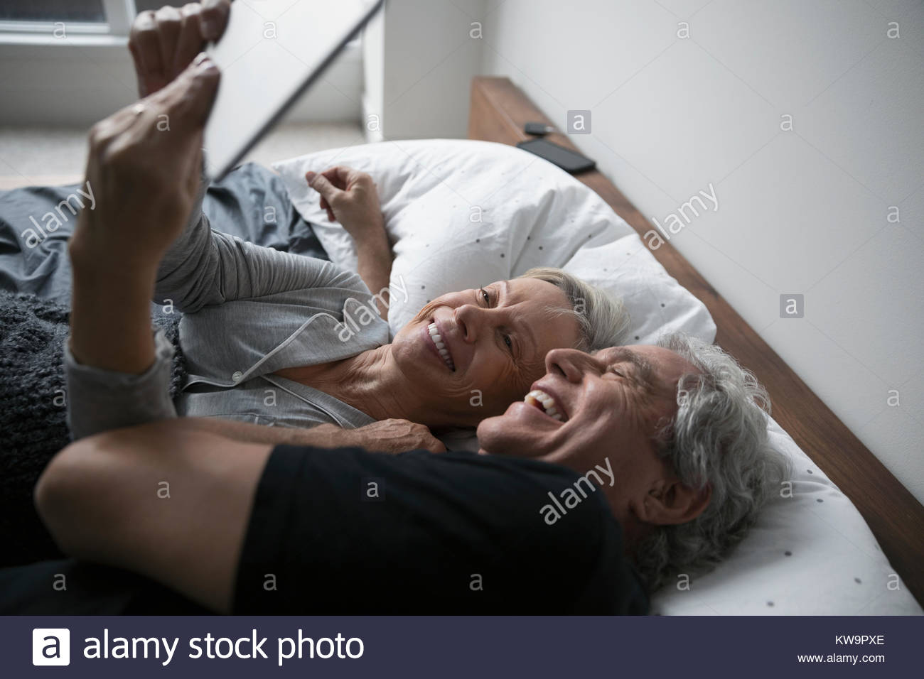 Affectionate,happy senior couple taking selfie with digital tablet,cuddling in bed - Stock Image