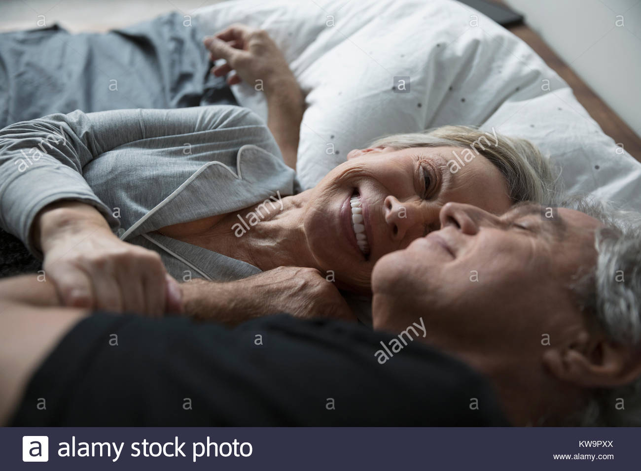 Affectionate,happy senior couple cuddling in bed - Stock Image