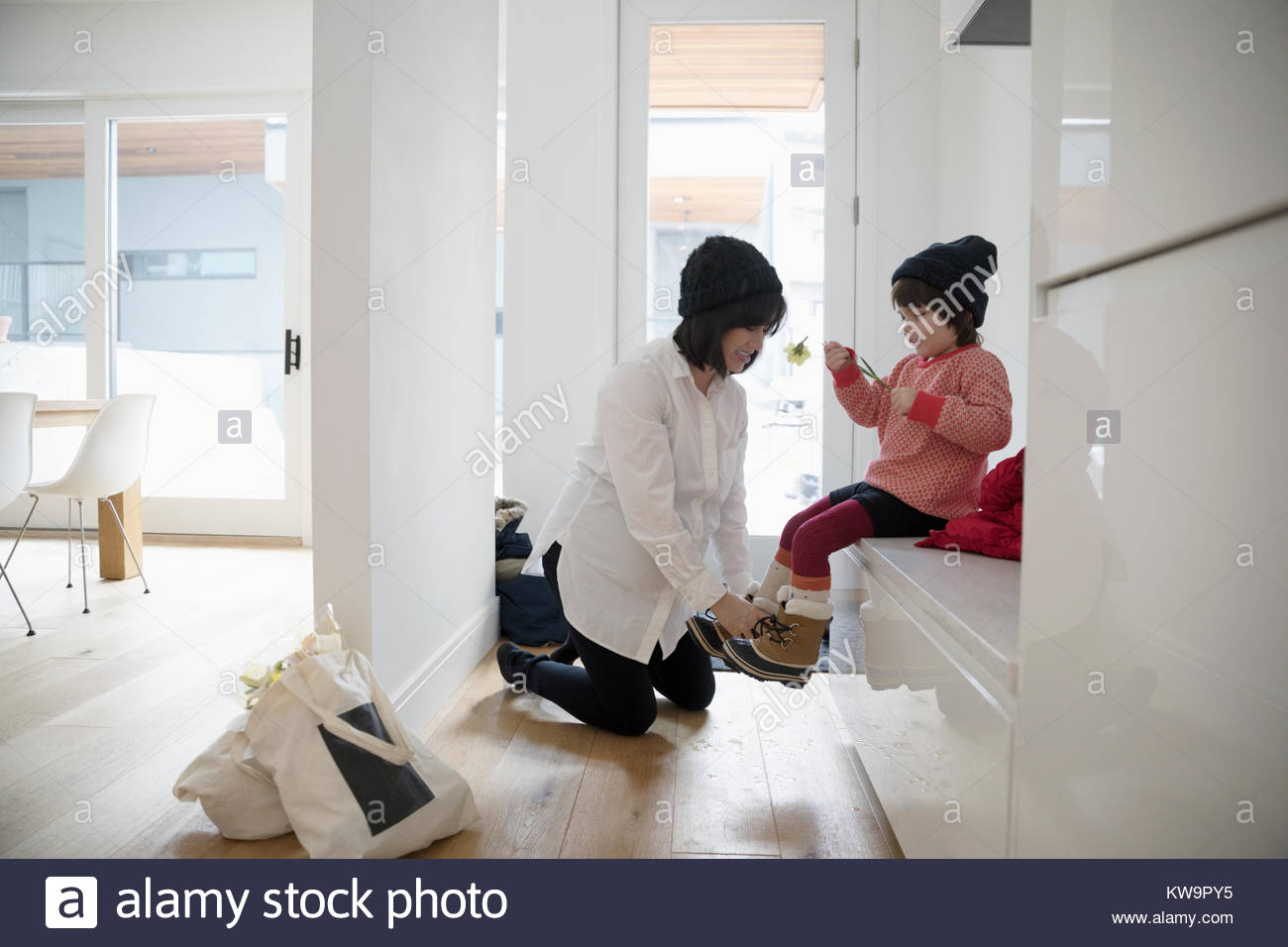 Pregnant mother putting boots on toddler daughter - Stock Image
