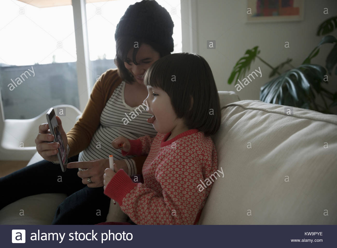 Pregnant mother showing smart phone to toddler daughter on sofa - Stock Image