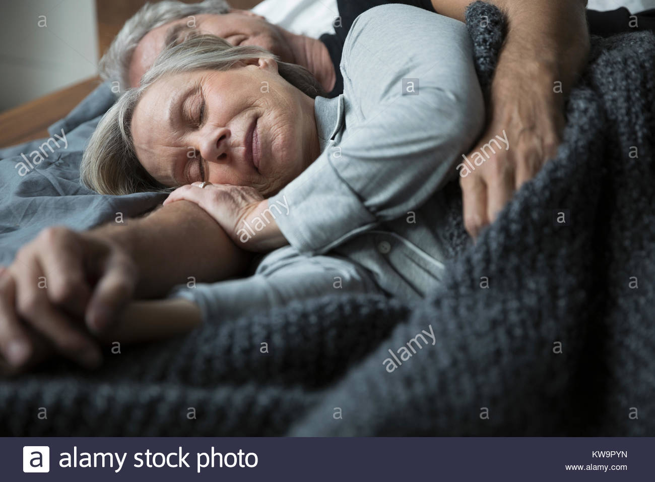 Serene senior couple sleeping in bed - Stock Image