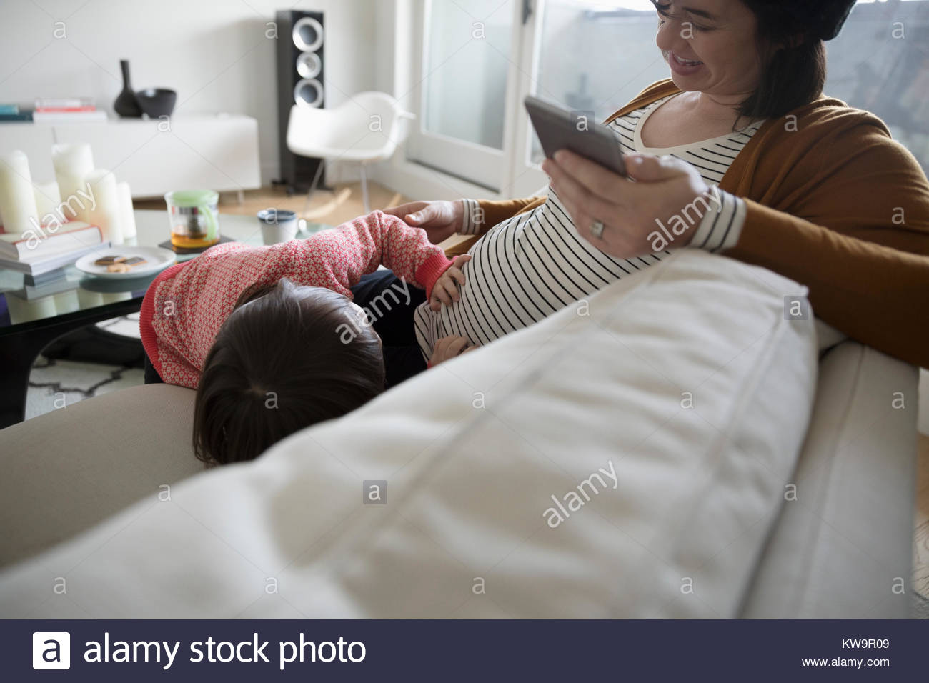 Toddler daughter touching pregnant mother - Stock Image