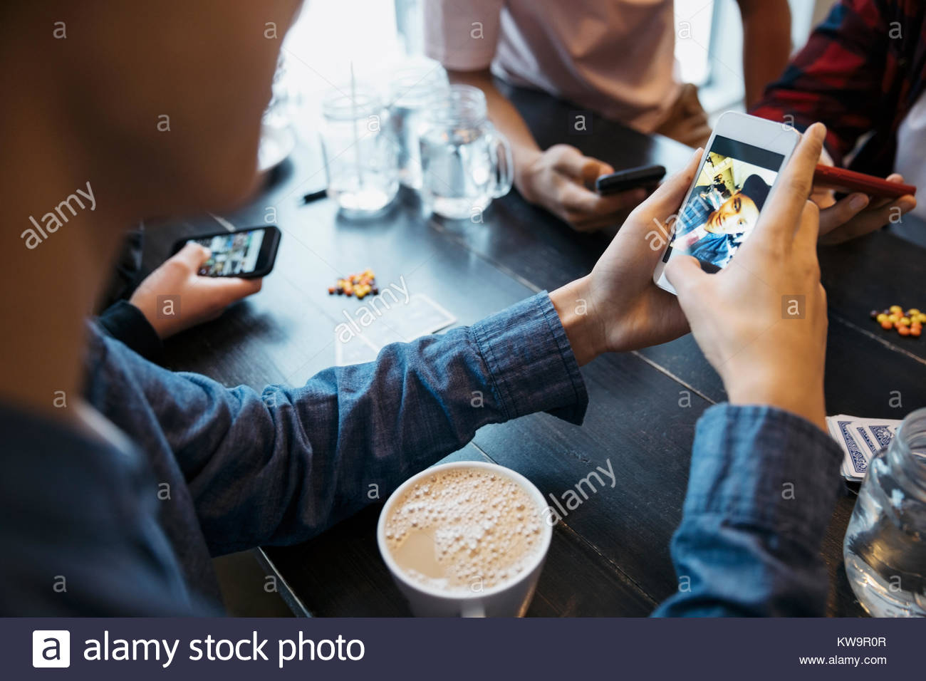 Tween boy using camera phone and drinking coffee at cafe table - Stock Image
