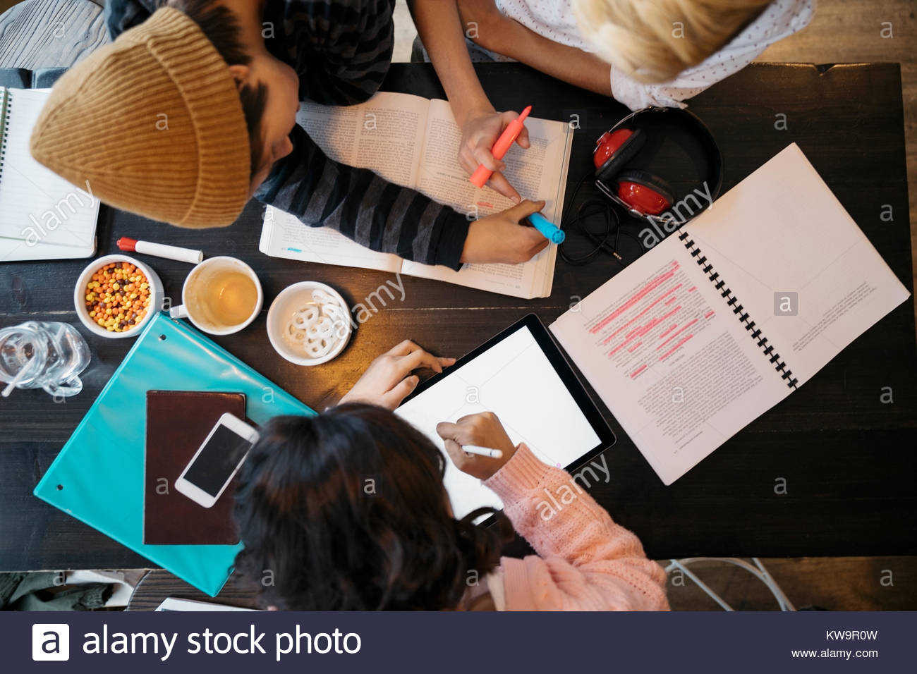 Overhead view high school students studying,highlighting textbook at cafe table - Stock Image