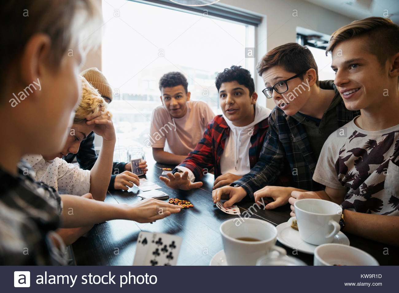 Tween boy friends playing cards and drinking coffee at cafe table - Stock Image