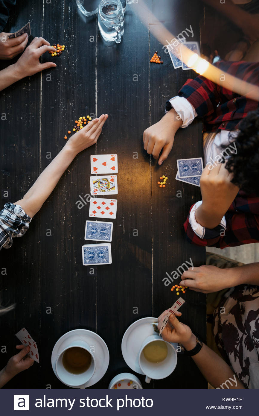 Overhead view tween friends playing cards with candy at table - Stock Image