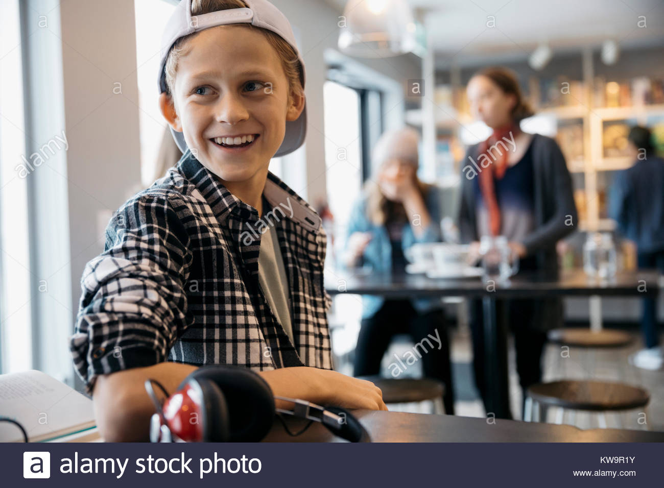 Smiling Caucasian high school boy student looking away in cafe - Stock Image