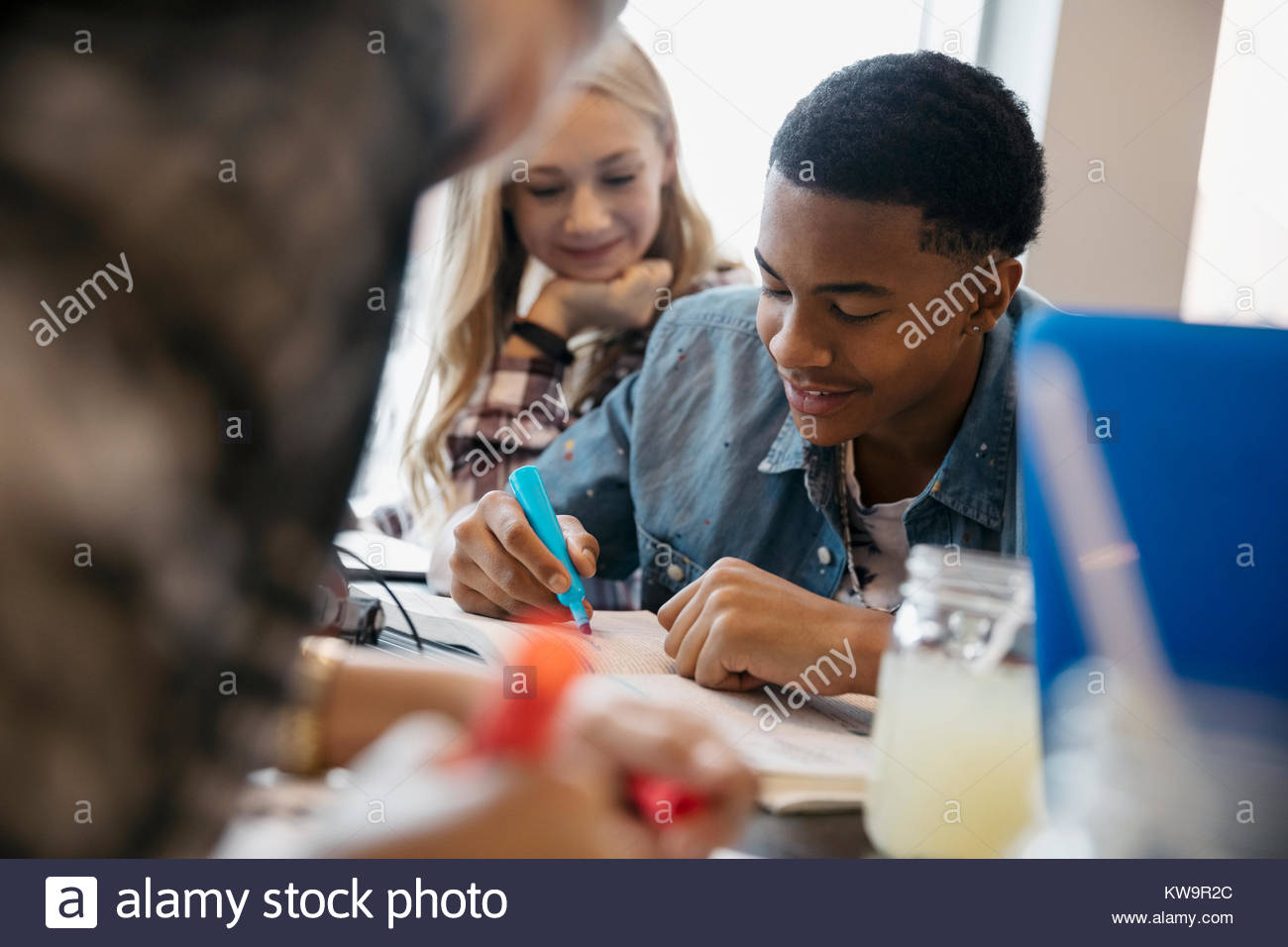 High school boy student studying,highlighting textbook in cafe - Stock Image