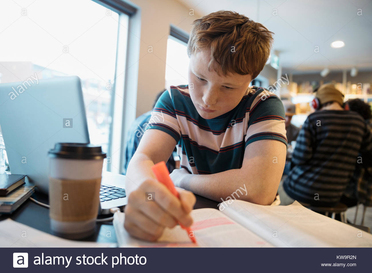 Serious high school boy student studying at laptop,highlighting textbook in cafe - Stock Image