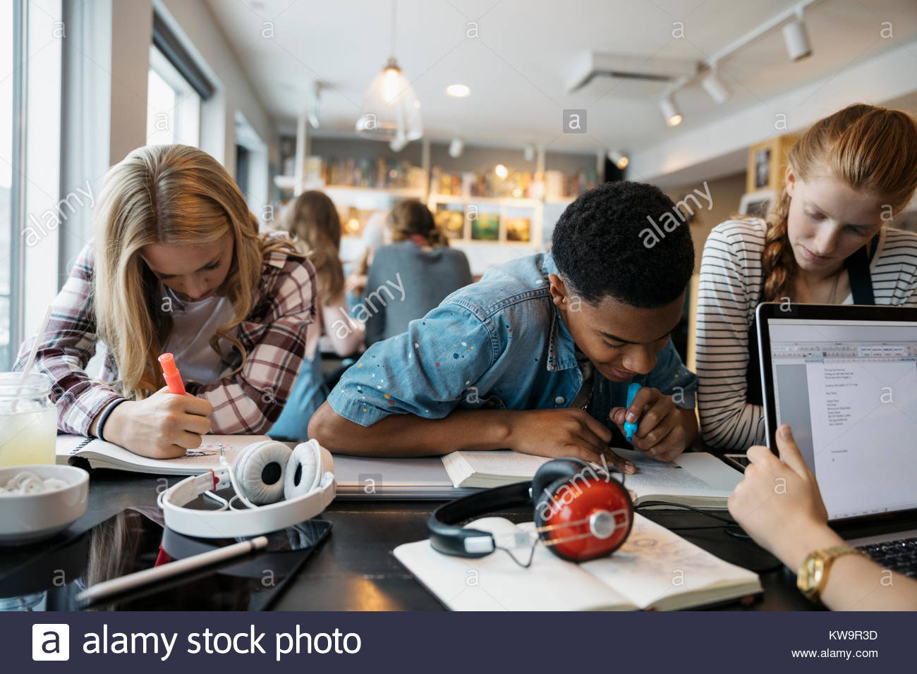 High school students studying at cafe table - Stock Image