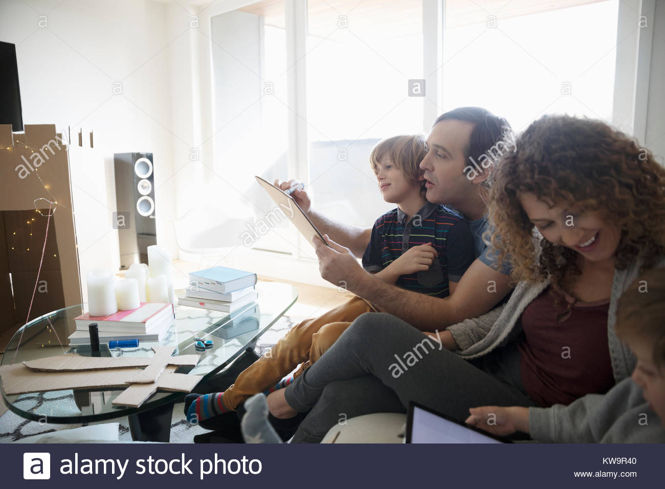 Family drawing and using digital tablet in living room - Stock Image