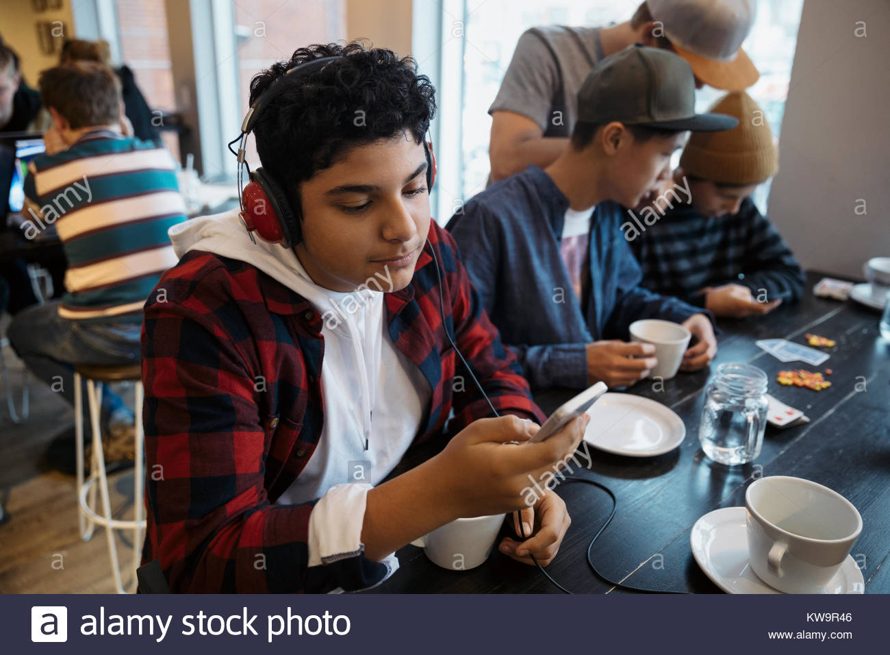 Middle Eastern tween boy with headphones listening to music with smart phone at cafe table - Stock Image
