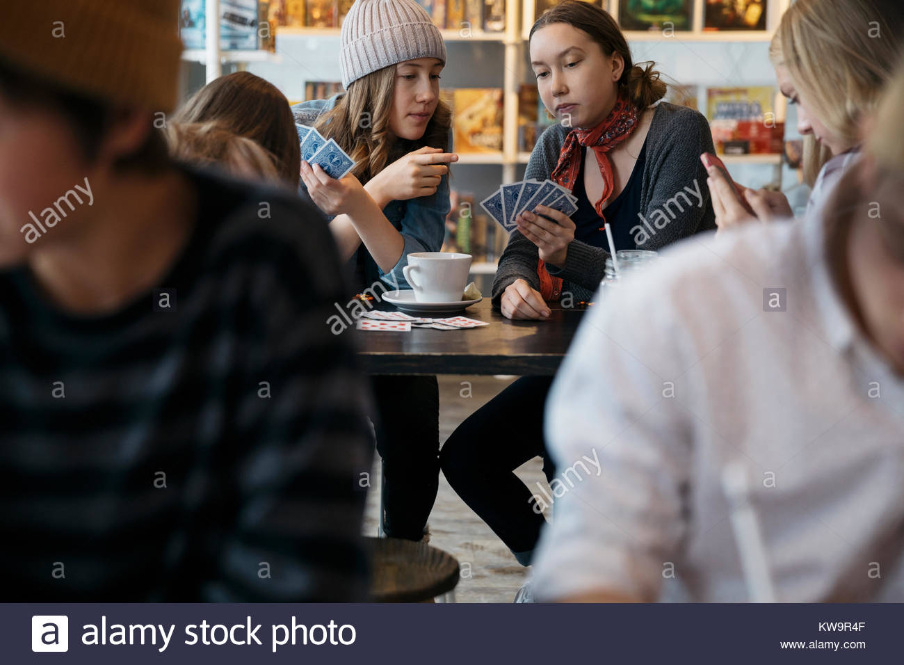 Tween girl friends playing cards at cafe table Stock Photo