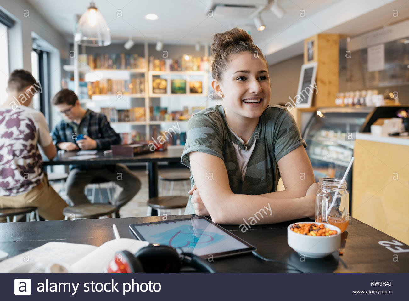 Smiling Caucasian high school girl student with digital tablet studying in cafe - Stock Image