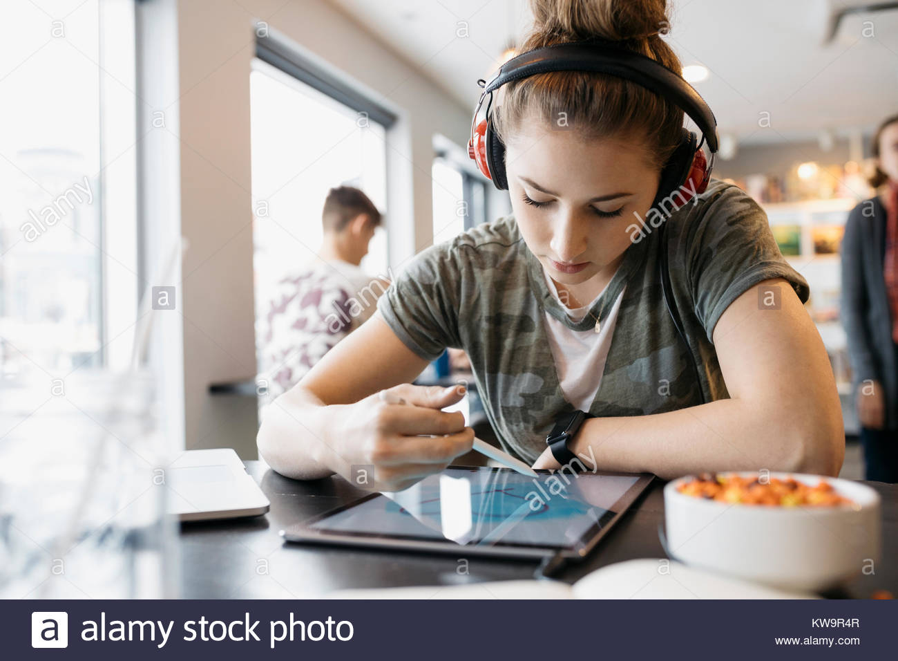 High school girl student with headphones using stylus,drawing on digital tablet in cafe - Stock Image