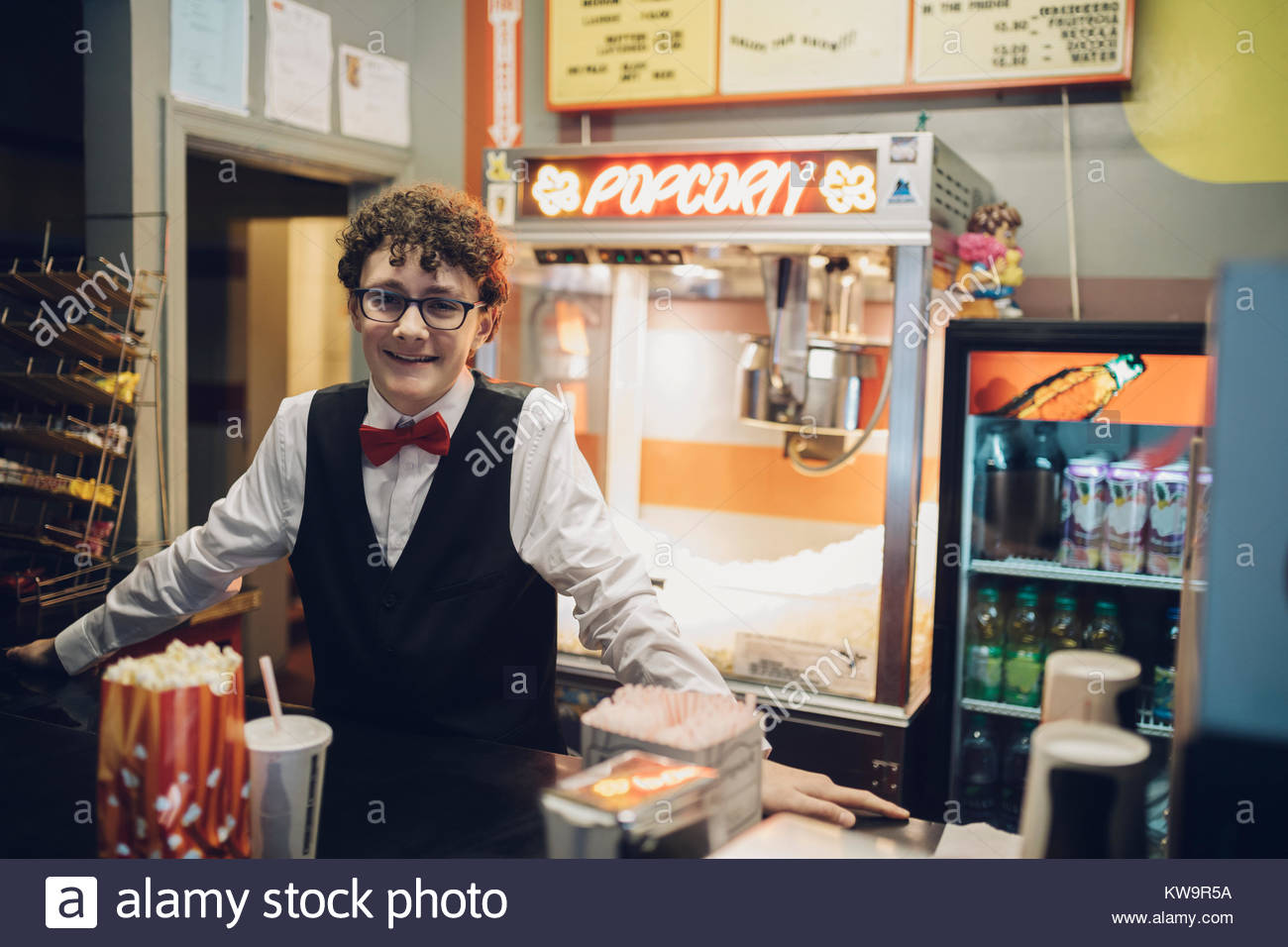 Portrait smiling,confident Caucasian tween boy working at refreshments concession stand in movie theater - Stock Image