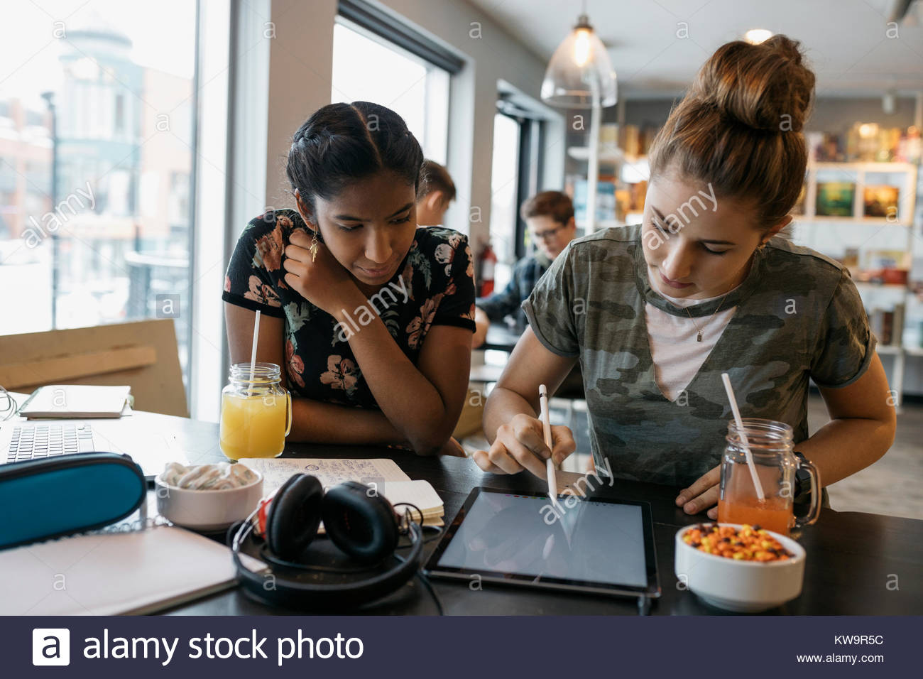 High school girl students studying,using stylus on digital tablet in cafe Stock Photo