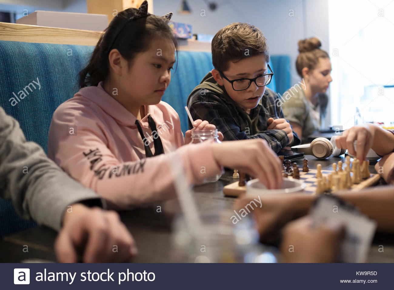 Tween friends playing chess at cafe table - Stock Image
