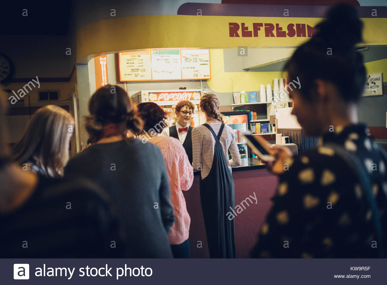 Tweens waiting in queue at refreshments concession stand in movie theater - Stock Image