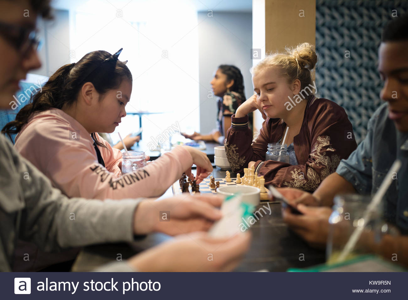 Tween girl friends playing chess at cafe table - Stock Image