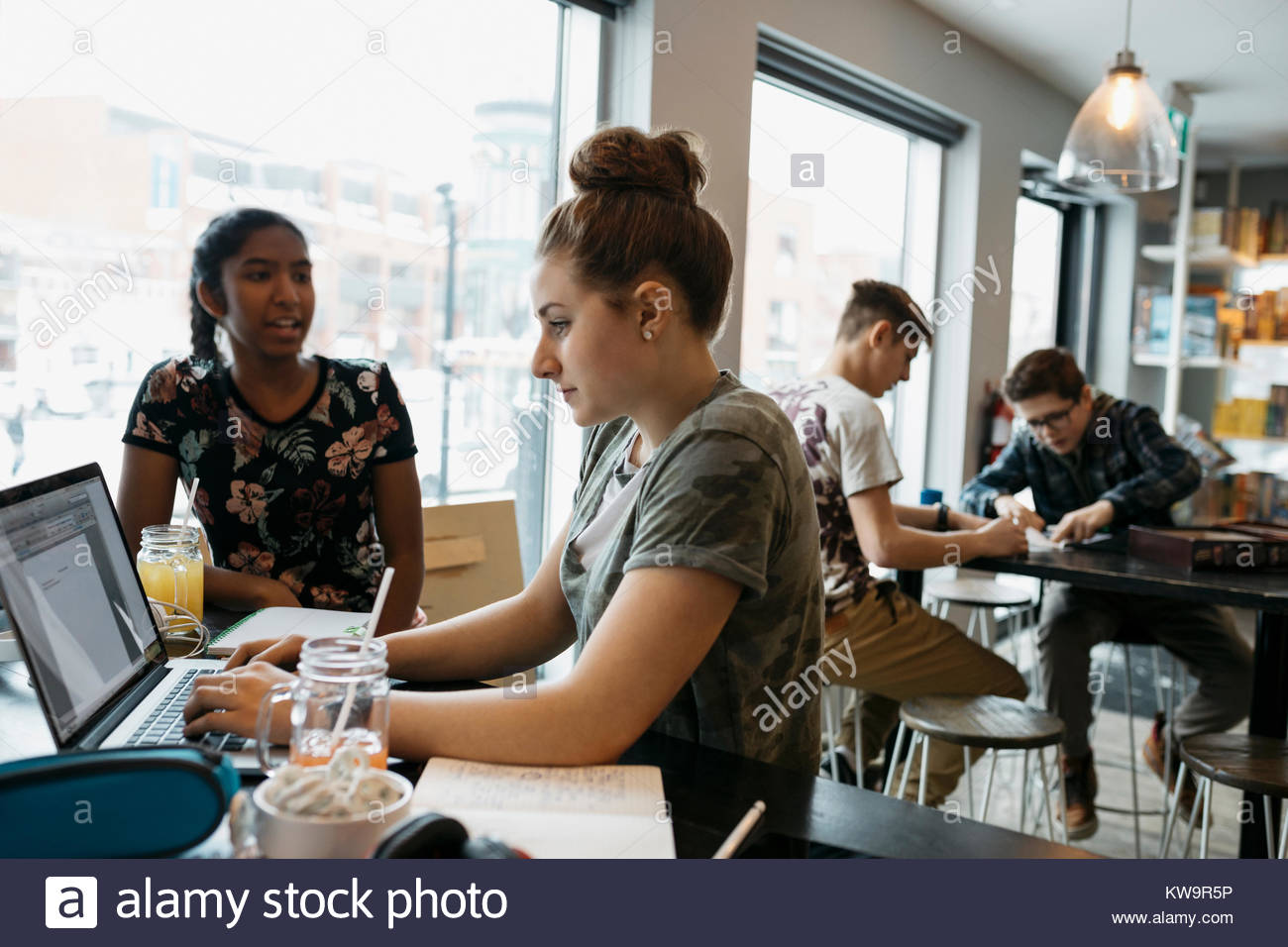 High school students studying,using laptop in cafe - Stock Image