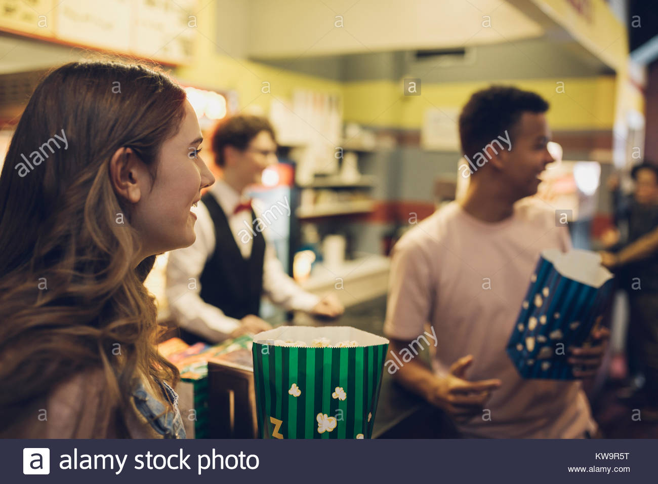 Smiling tween friends with popcorn at refreshments concession stand movie theater - Stock Image