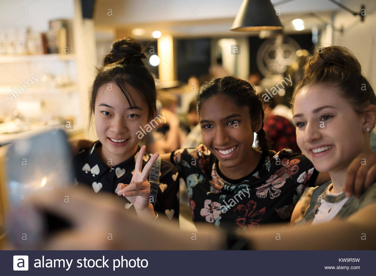 Smiling tween girl friends taking selfie with camera phone in cafe Stock Photo