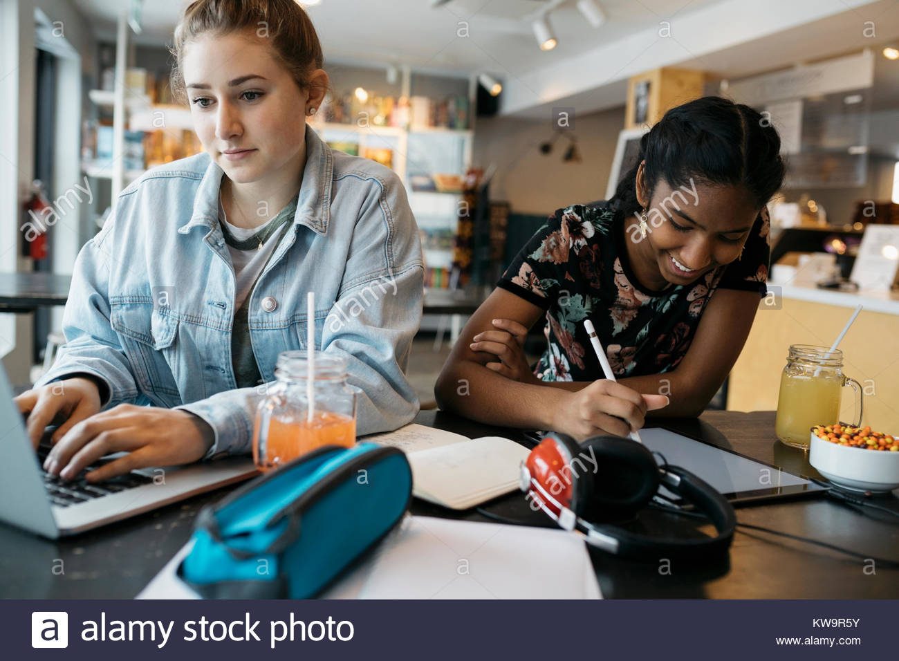 High school girl students studying,using laptop in cafe Stock Photo