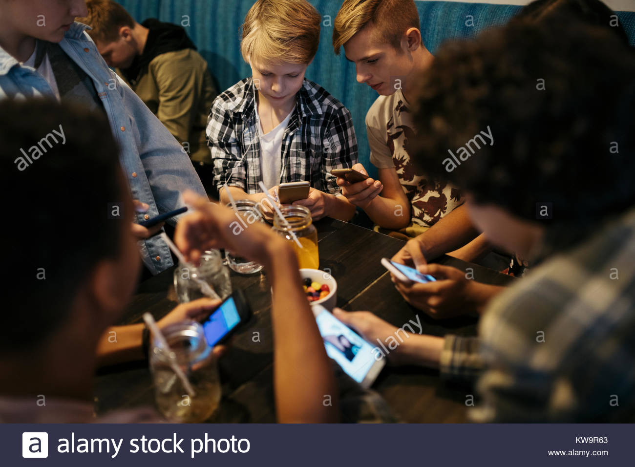 Tween boy friends texting with smart phones,hanging out at cafe table - Stock Image