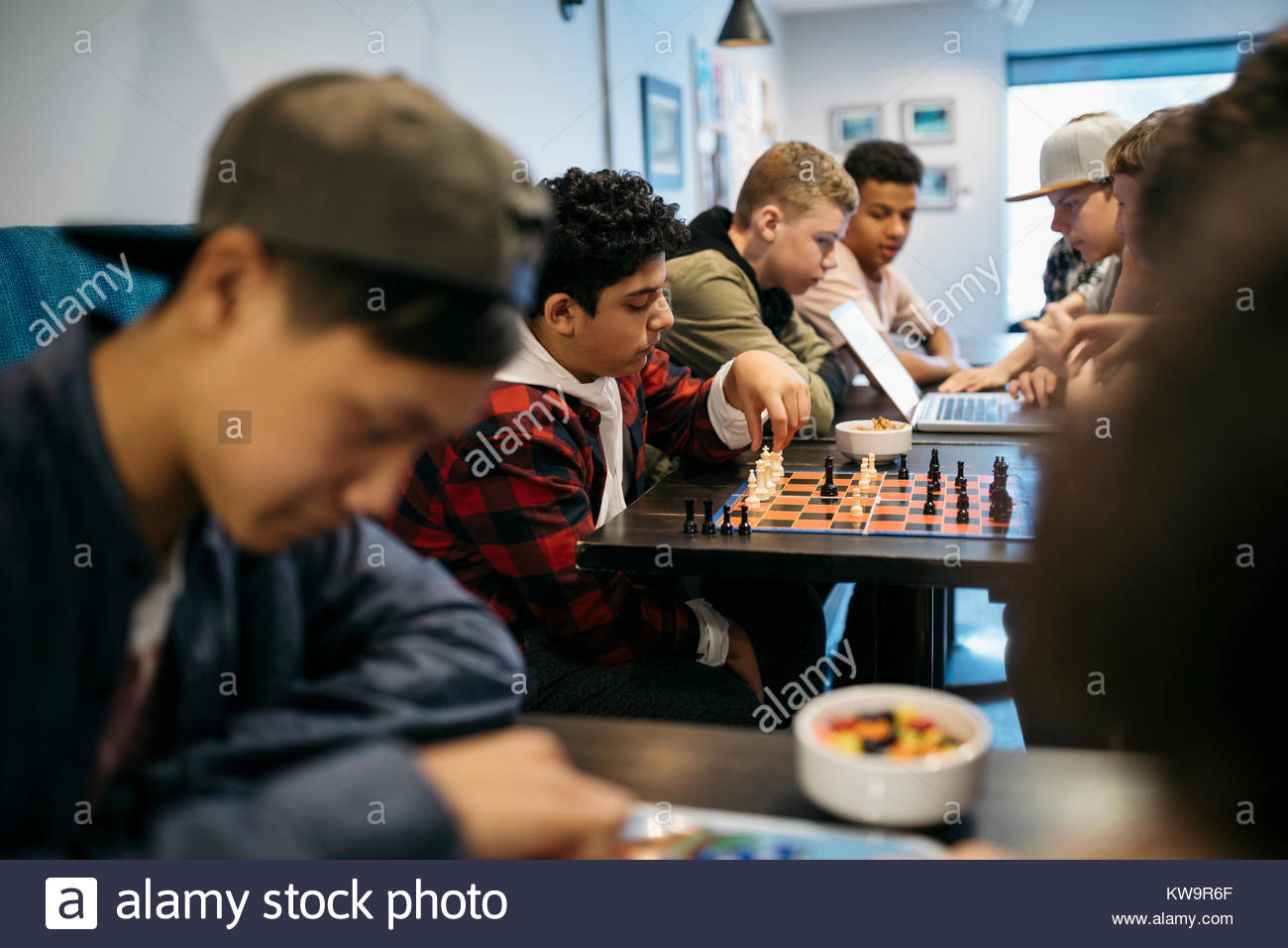 Tween boy friends playing chess at cafe table - Stock Image
