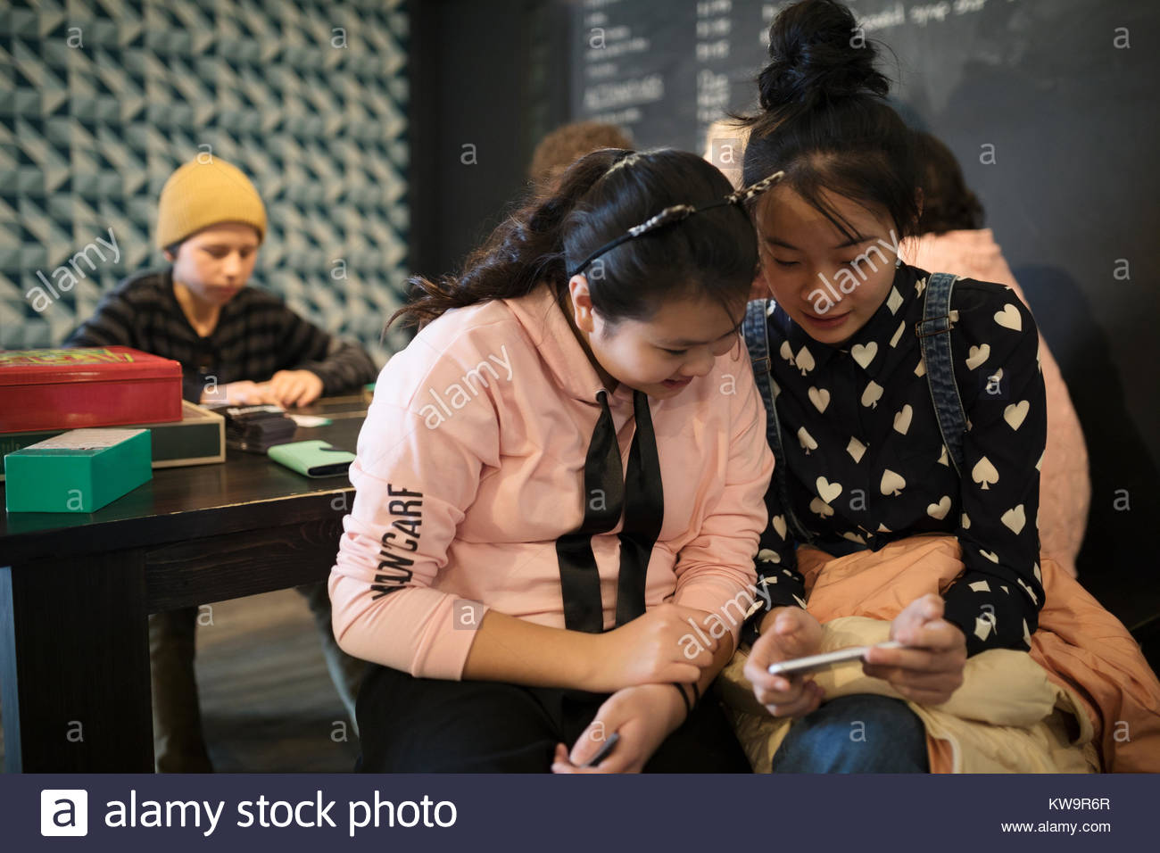 Asian tween girl friends texting with smart phone in cafe - Stock Image