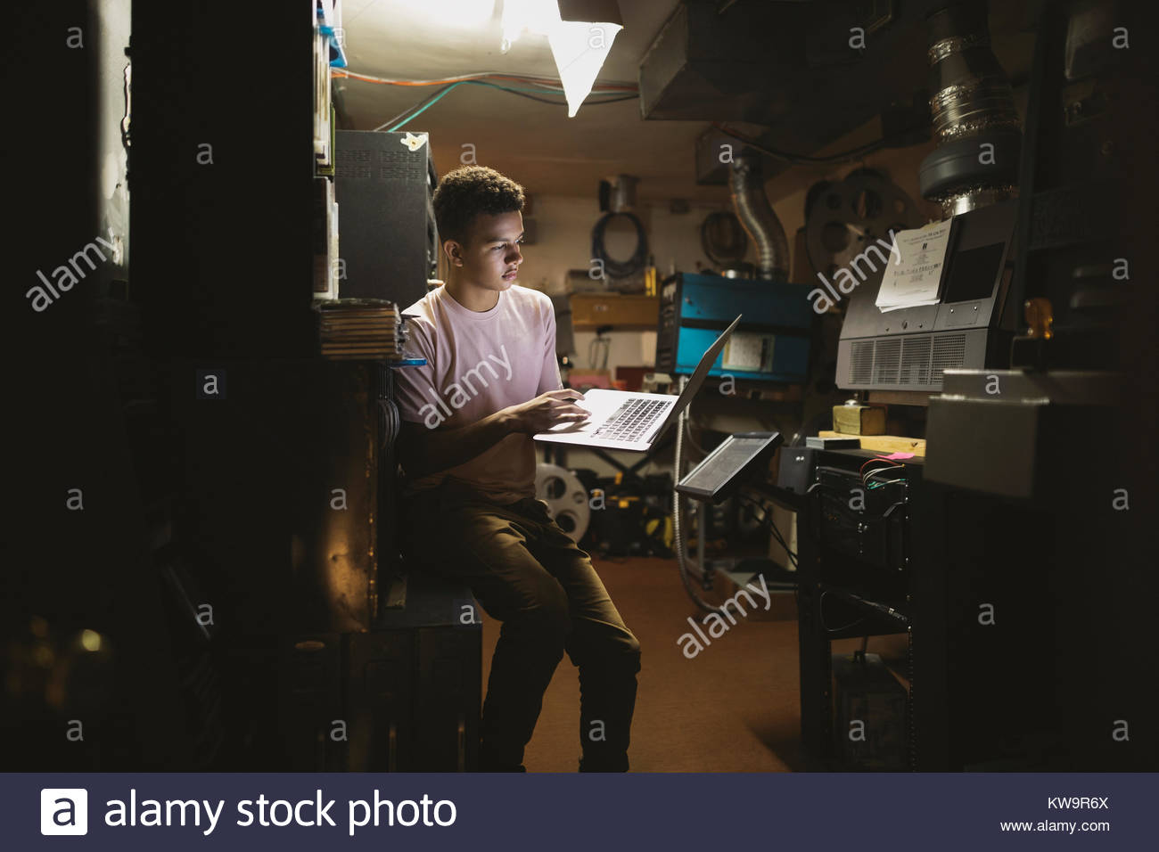 Mixed race tween boy projectionist using laptop in movie theater - Stock Image