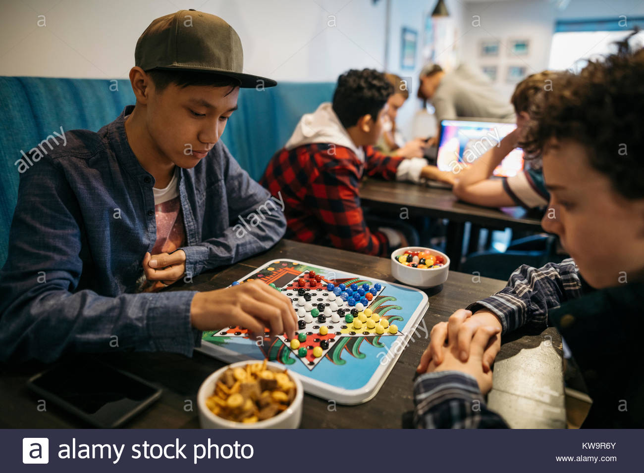 Tween boy friends playing Chinese checkers at cafe table - Stock Image