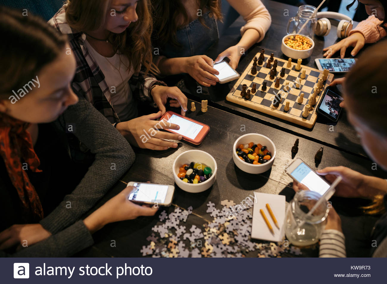 Tween girl friends playing chess,assembling jigsaw puzzle and texting with smart phones at table - Stock Image