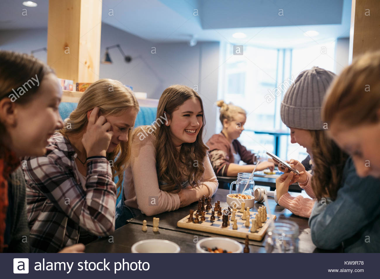 Tween girl friends playing chess,hanging out at cafe table - Stock Image
