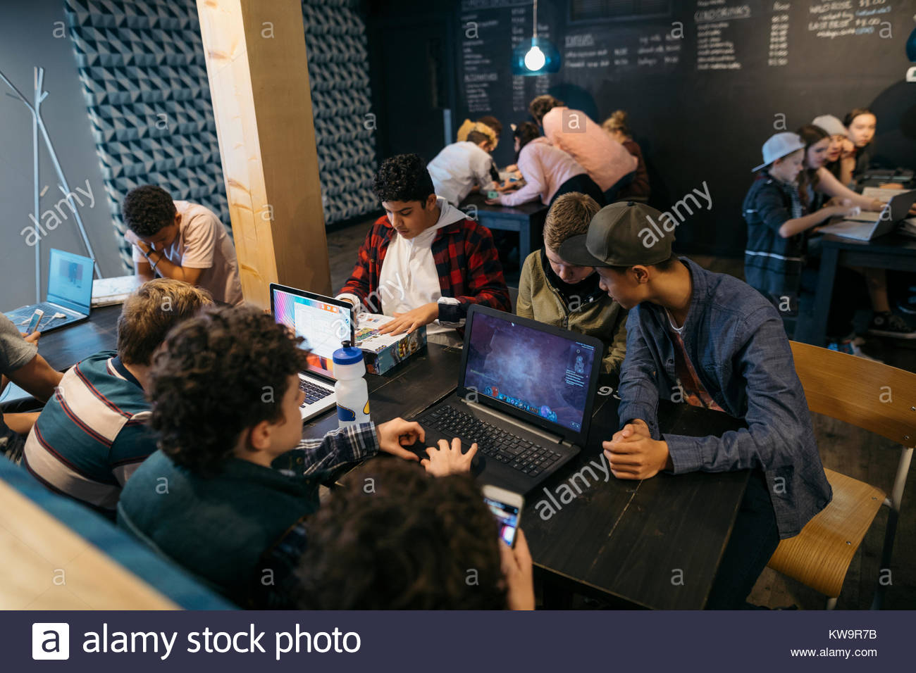 High school students studying at laptops in cafe - Stock Image
