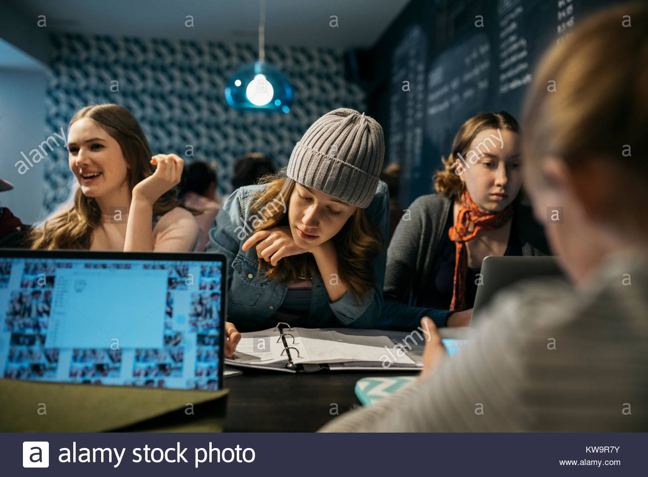 Girl high school students studying in cafe - Stock Image