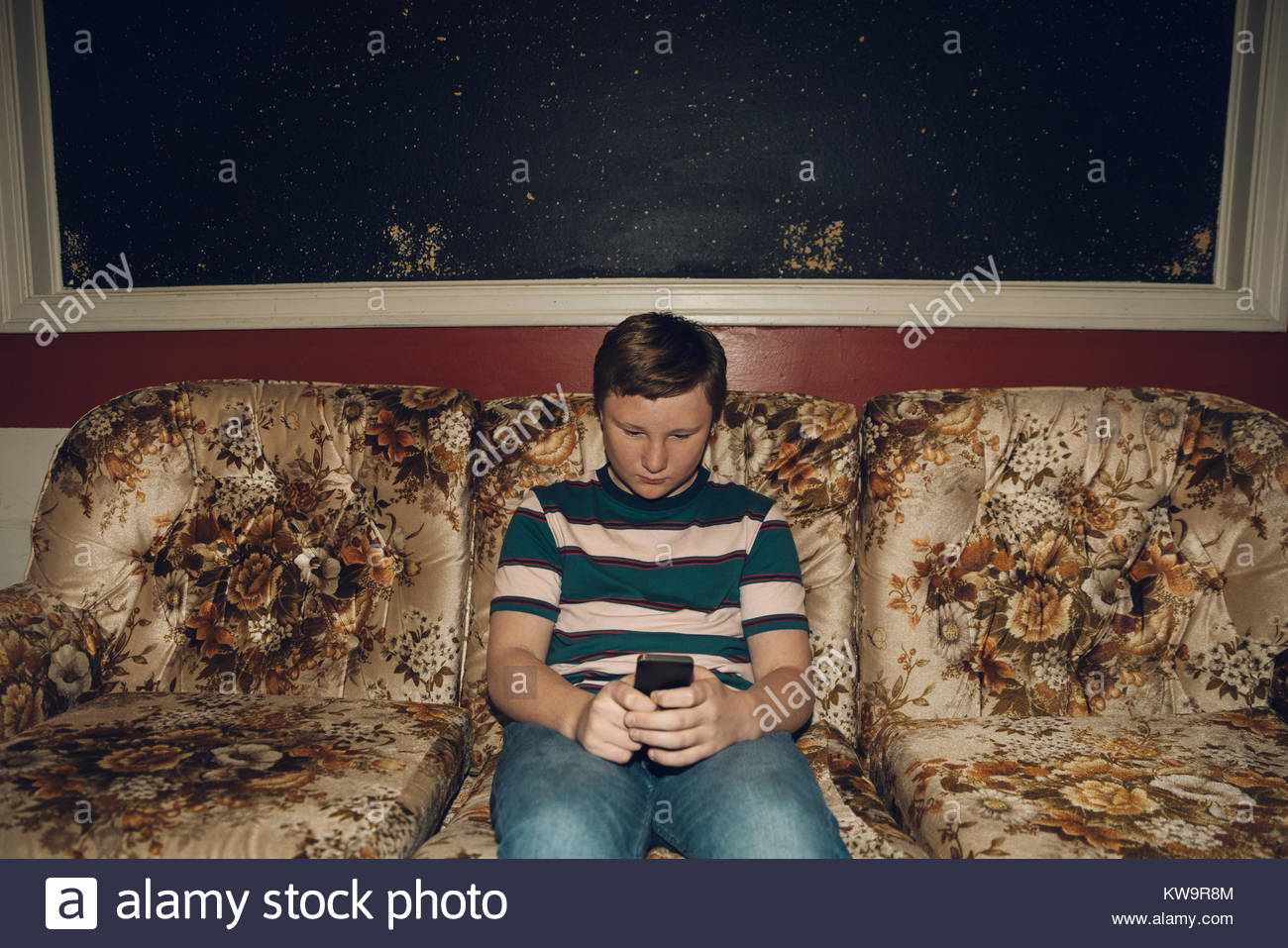 Caucasian Tween Boy Texting With Smart Phone On Old Floral Sofa