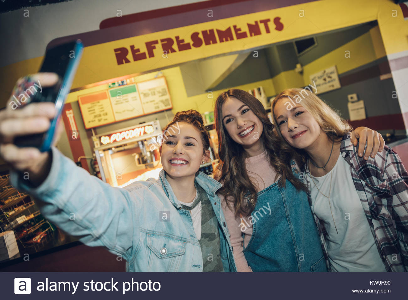 Smiling,enthusiastic Caucasian tween girl friends taking selfie with camera phone in movie theater - Stock Image
