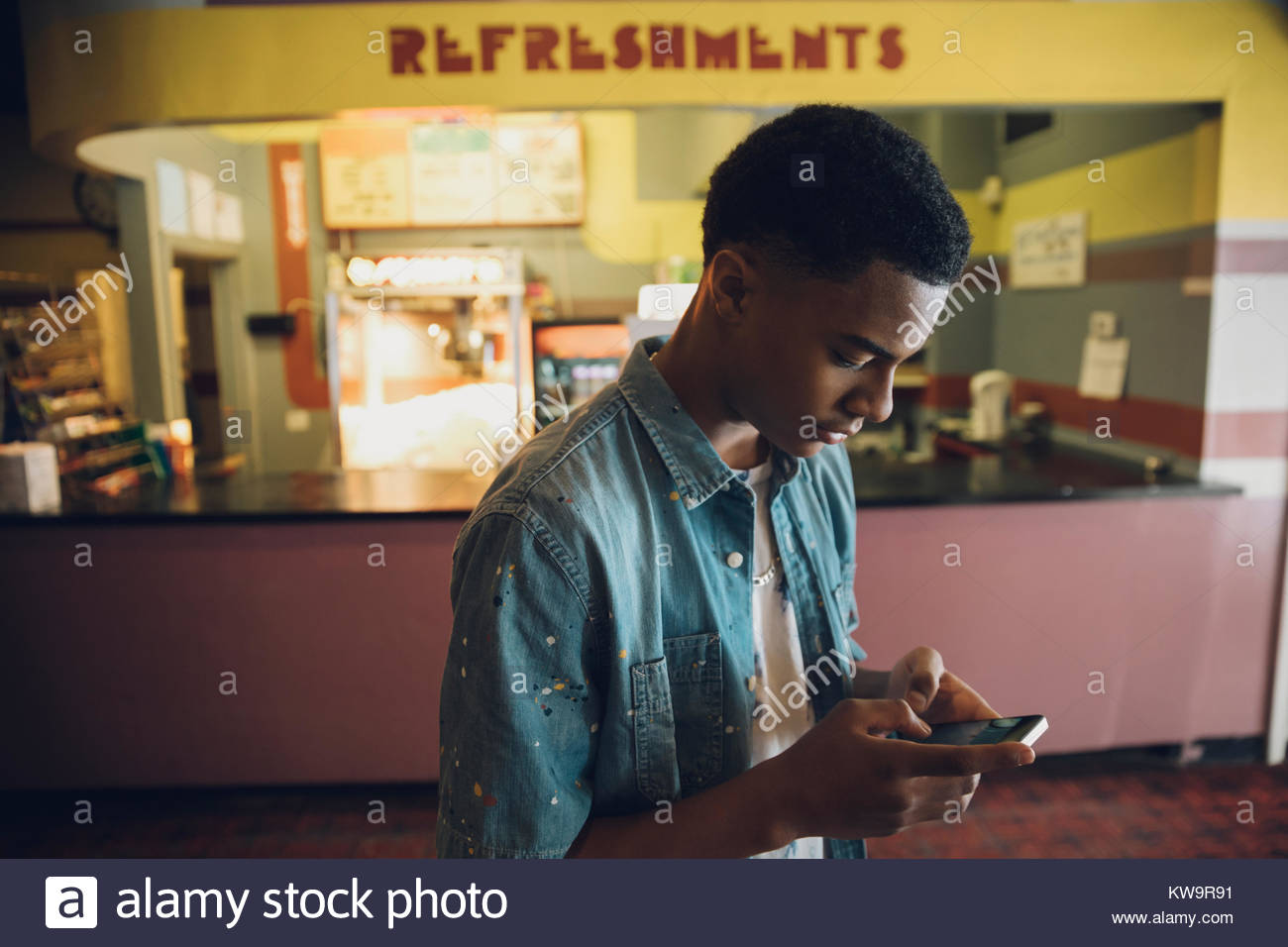 African American tween boy texting with smart phone in movie theater - Stock Image