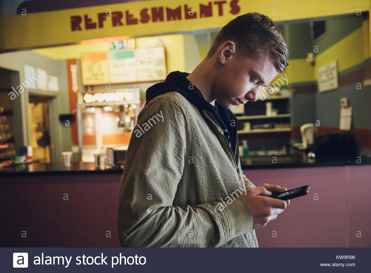 Caucasian tween boy texting with smart phone at refreshments concession stand in movie theater lobby - Stock Image