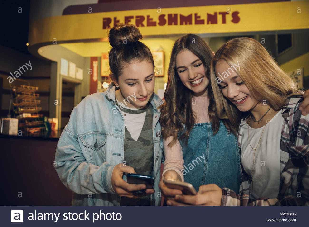 Smiling Caucasian tween girl friends texting with smart phones at movie theater - Stock Image