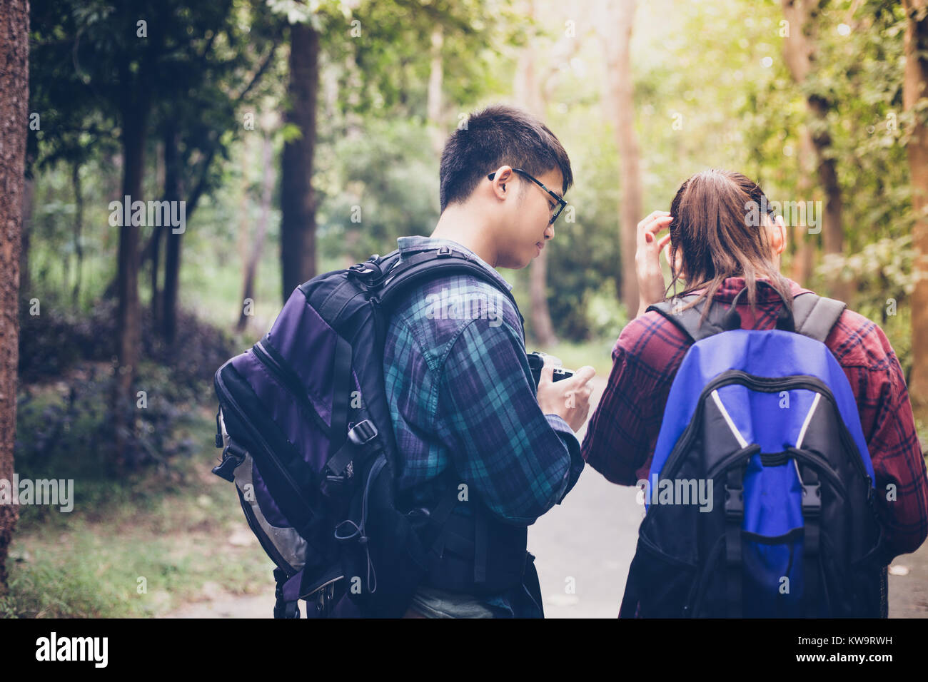 Asian Group of young people Hiking with friends backpacks walking together and looking map and taking photo camera - Stock Image