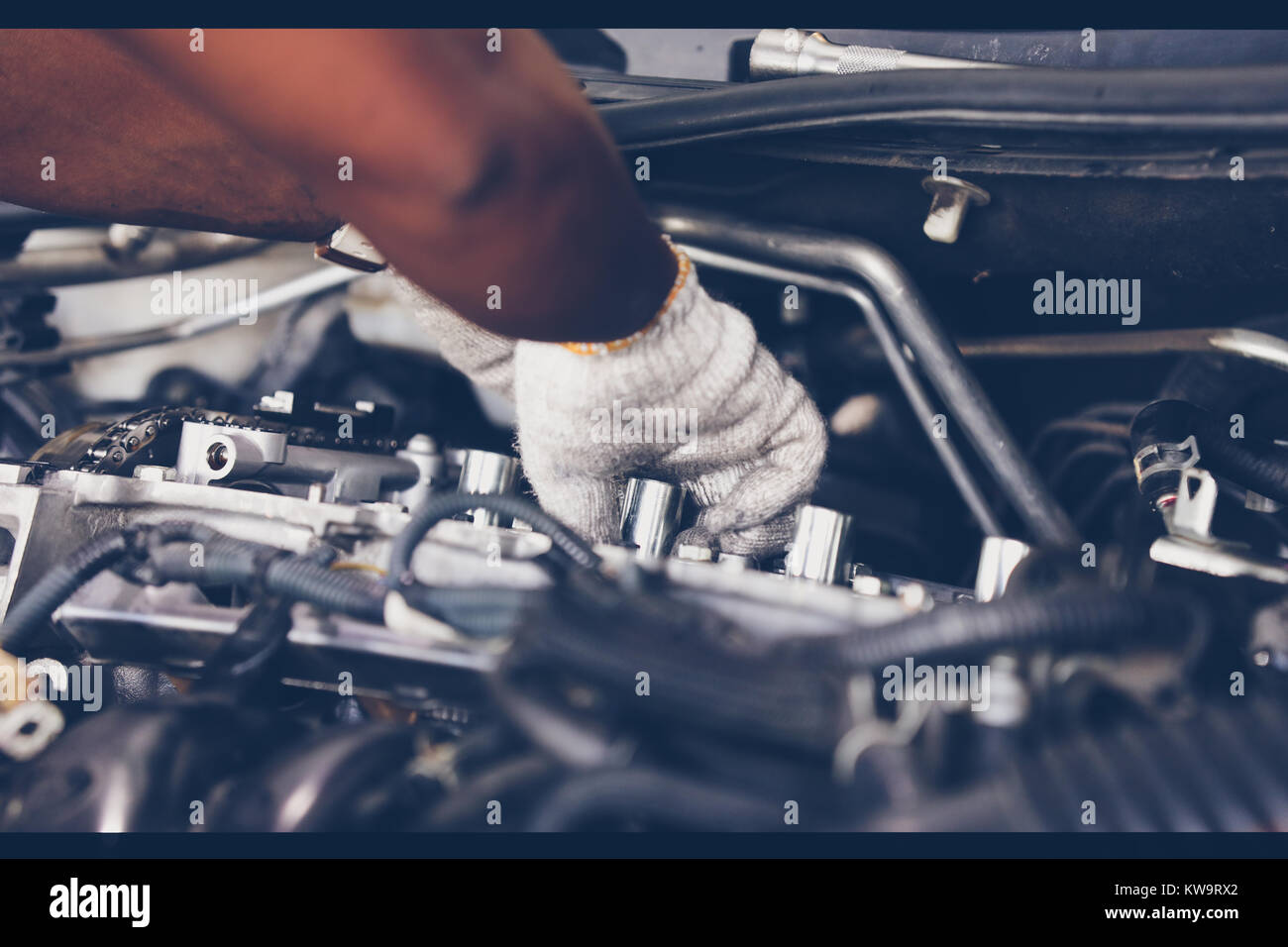 Hands of auto mechanic repairing car. Selective focus. - Stock Image