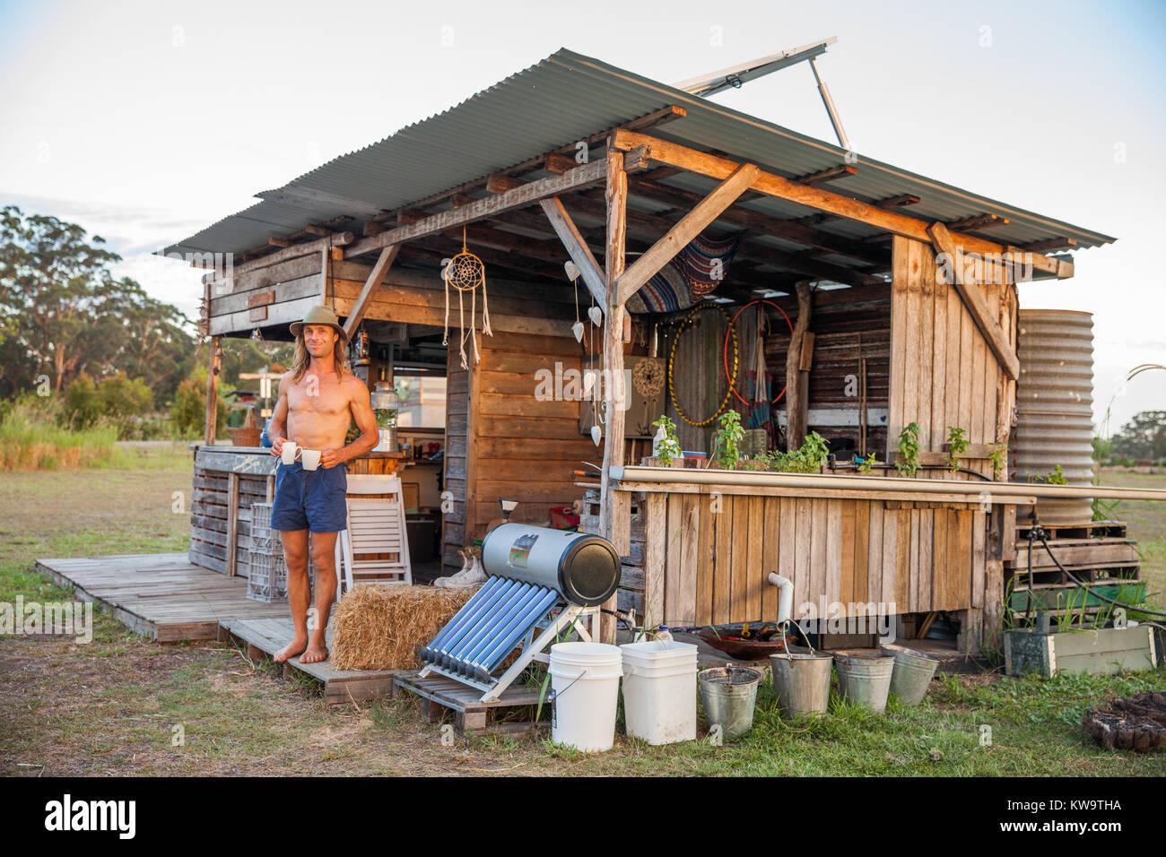 Man outside Off grid shack or shed in Australian bush - Stock Image