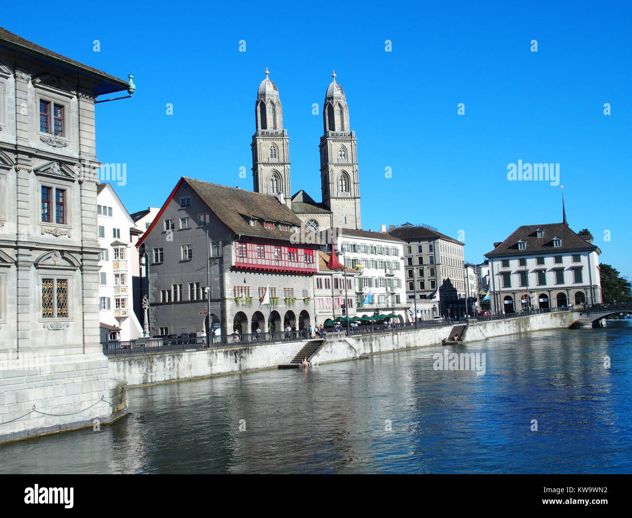 White houses on bank of Limmat river in ZURICH city and cityscape of largest swiss center in SWITZERLAND with alpine - Stock Image