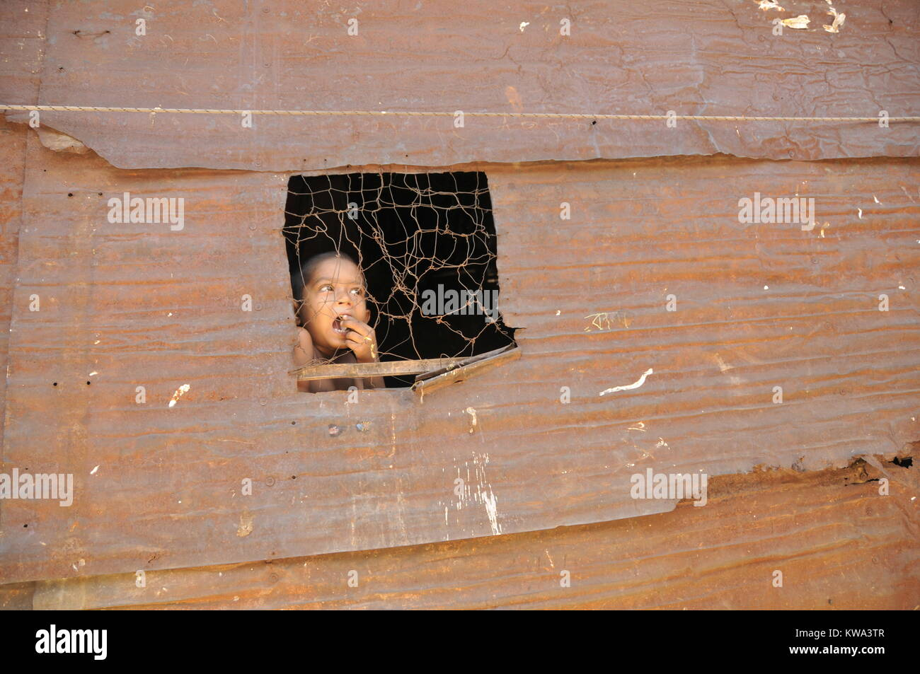 A kid looks at the sky through a narrow window in a shanty house at Korail slum in Dhaka, capital of Bangladesh - Stock Image