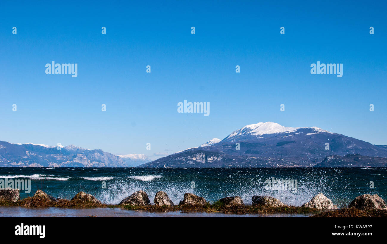 Landscape of a lake with waves and squirts on a windy day, background with alpine mountains - Stock Image