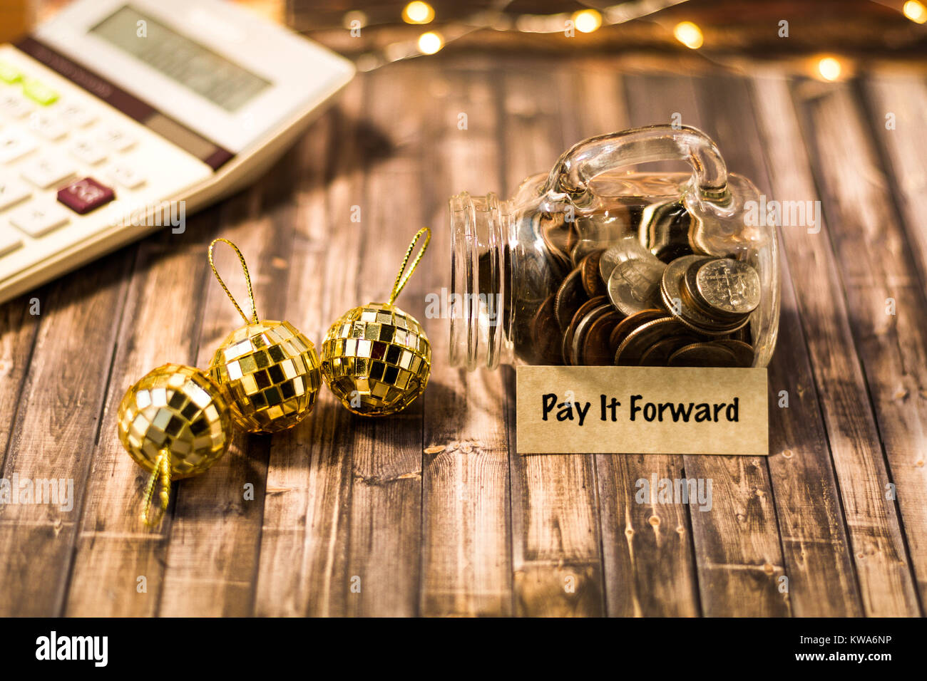 Pay it Forward money jar savings motivational concept on wooden board - Stock Image